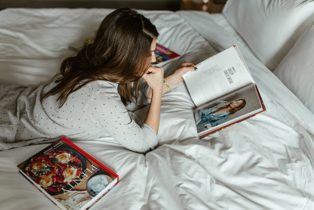 genevieve padalecki of now&gen wife of jared padalecki of supernatural lies on bed with cookbooks reading a cookbook