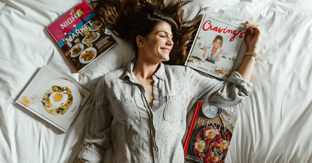 genevieve padalecki wife of jared padalecki of supernatural lies on bed with cookbooks around her