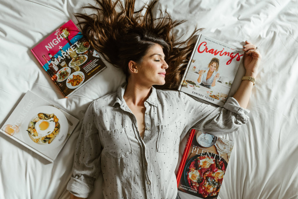 genevieve padalecki of now&gen wife of jared padalecki of supernatural lies on bed with cookbooks around her head